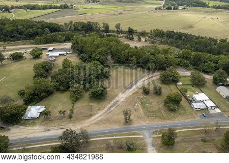 Aerial Perspective Of Small Township Showing Cattle Yards, Show Ring And Homes Bordered By A Creek A