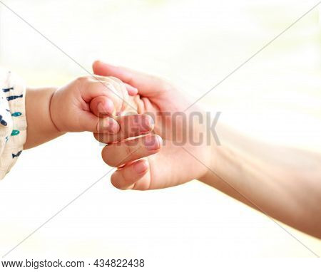 Family Scene , Close Up Parent And Baby Holding Hands Together And White Background With Copy Space.
