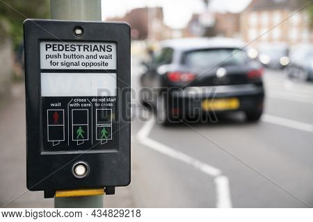 Pedestrains Push Button And Wait For Signal Opposite At Crosswalk, Traffic Light At Square In Urban