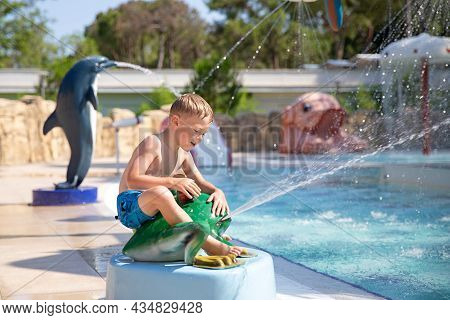A Smiling Cute Boy Has Fun In The Pool At The Aquapark. Activities In The Pool. Concept Summer Vacat