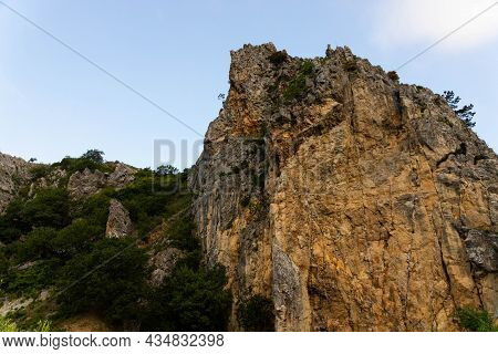 Large Wild Red Limestone Cliffs With Sparse Vegetation.
