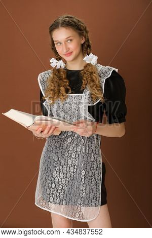 Pretty Girl In Retro School Uniform Reading Book. Curious Graduate Teenage Girl With Braided Hair We