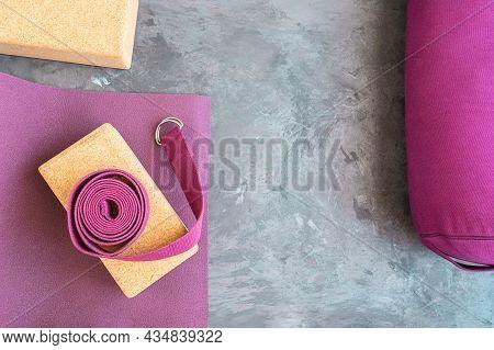 Open Yoga Mat, Cork  Block,  Yoga Belt  And Bolster. Essentials Yoga Props Background. Copy Space.