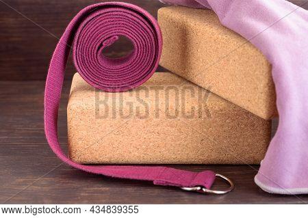Two Cork Blocks, Violet Yoga Strap And Lilac Towel  For Doing Yoga On Wooden Floor. Yoga Props Backg