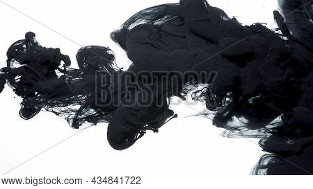 Drops Of Black Ink In Water. Colored Acrylic Paints In Water. Black Watercolor Ink In Water On A Whi