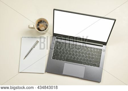 Mockup Computer Laptop With White Blank Screen, Notepad, Coffee Cup And Copy Space On White Backgrou
