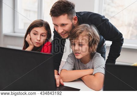 Smart Elementary Schoolkids With Male Teacher Looking At Laptop Screen With Interest While Testing P