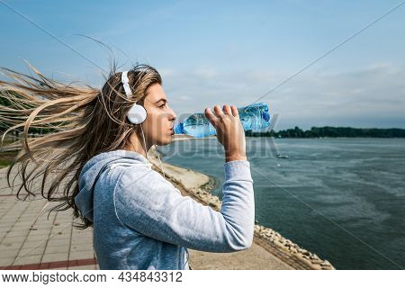 Young Beautiful Fitness Sporty Jogger Woman Standing Near River Drinking Water For Hydration After C