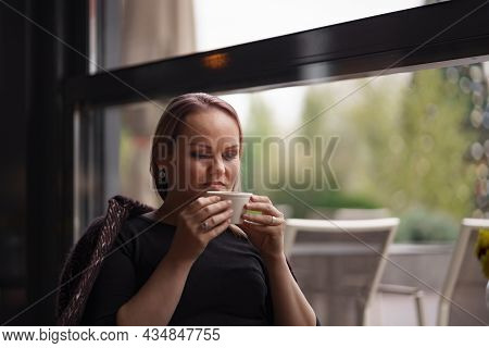 Close-up Portrait Of Smiling Woman Drinking Coffee Alone. Lovable Lady Standing Near Window And Look