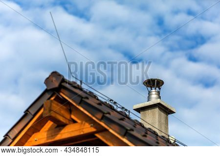 Stainless Steel Metal Chimney Pipe On The Roof Of The House Against The Blue Sky. Stainless Steel Ch