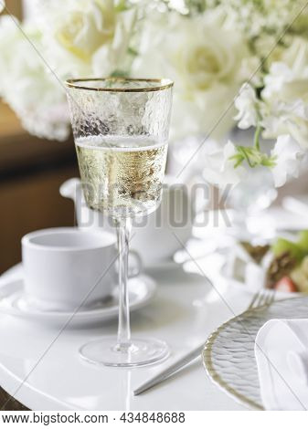 Table Serves For Banquet. Champagne In Modern Stylish Wine Glass, Plates With Napkins And Shiny Cutl