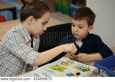 Two Kids Of Different Age Choose Parts Of Robotic Electric Toys For Building Robots At Robotics Scho