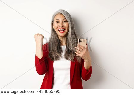 Asian Old Woman Winning Online, Holding Smartphone And Making Fist Pump Gesture To Celebrate Win, Tr