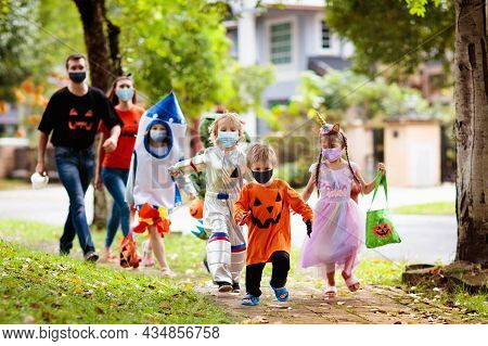 Kids Trick Or Treat In Halloween Costume And Face Mask. Children In Dress Up With Candy Bucket In Co
