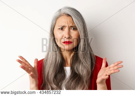 Close Up Of Confused Asian Female Manager With Grey Hair, Wearing Red Blazer And Makeup, Spread Hand