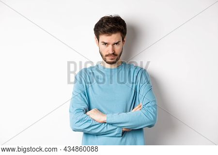 Image Of Offended And Sad Young Man With Beard, Look From Under Forehead And Sulking Irritated, Cros