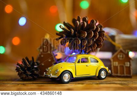 Vladimir, Russia-october 2021: Small Toy Yellow Car With A Big Beautiful Christmas Tree Cone On The