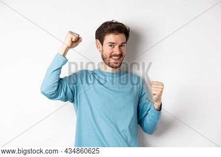 Happy Bearded Man Celebrating Victory, Raising Hands Up And Triumphing, Winning Prize And Smiling Wi