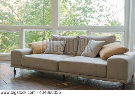 Large Cozy Sofa On Wheels Against The Background Of A Window To The Floor. Cozy Empty Living Room In