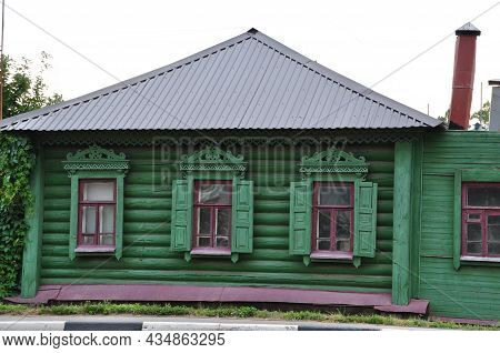 Old Wooden House. The Log House Is Painted Green. House Windows With Shutters And Carved Frames.