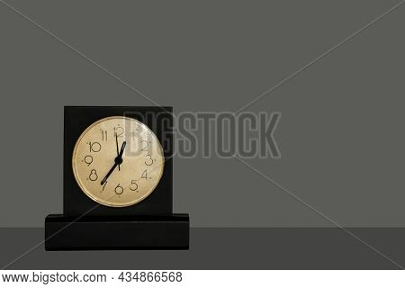 Black Table Clock With White Dial Standing On Dark Table Isolated On Dark Background