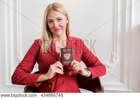 Attractive Blonde Woman In A Red Dress Holds A National Passport Of A Citizen Of The Russian Federat