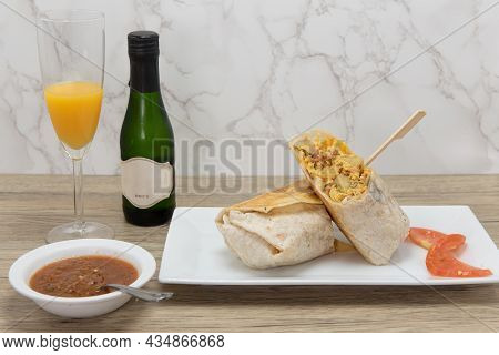 Loaded Breakfast Burrito With Meat And Eggs Cut In Half For Easier Handling Served With Orange Juice