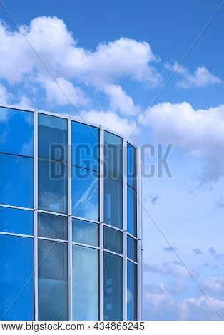 Low Angle View Of Curved Glass Office Building Against White Clouds On Blue Sky Background In Vertic