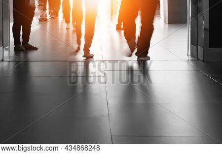 Silhouette Motion Blur Of People Legs Are Walking Into The Building With Flare Light And Shadow On S