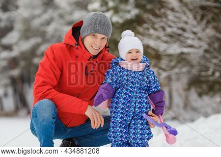 Smiling Little Girl Having Fun With Father In Winter Park. Cute Two Year Old Kid With Parent Playing