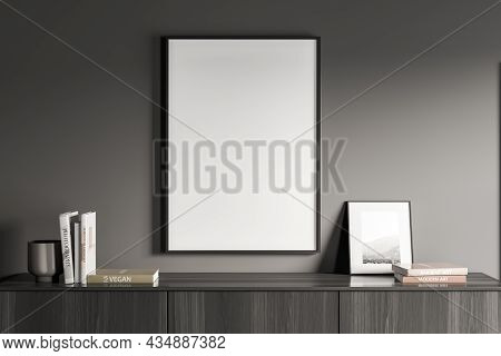 Empty White Canvas On Grey Wall Of Living Room Interior With Books And Photo Frame On Top Of Modern