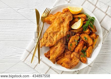 Breaded Chicken Cutlets With Oven Roasted Potato Wedges On A White Plate On A White Wooden Table Wit