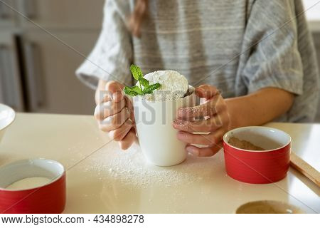 child's hand holding eggs, baking ingredients on white kitchen table, baking at home with kids, cake in a mug preparation.