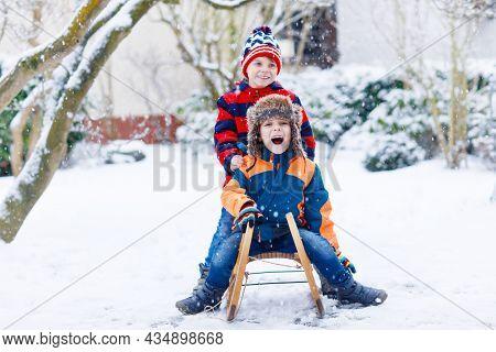 Two Kid Boys Having Fun Sleigh Ride During Snowfall. Children Sledding On Snow. Siblings Riding A Sl