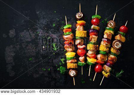 Chicken kebabs on skewers with mushrooms and vegetables on dark background