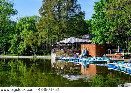 Vivid Green Landscape With Old Large Linden Trees And Small Boats Near The Lake In Cismigiu Garden (