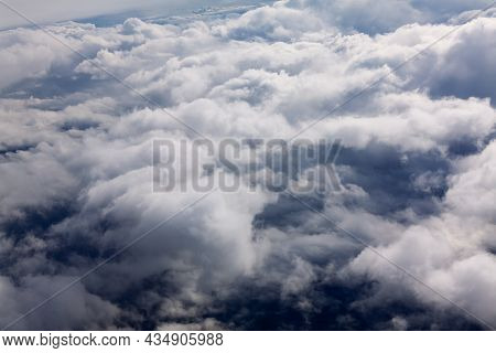 Flying Above Fluffy Cumulus Clouds . Dramatic Cloudscape