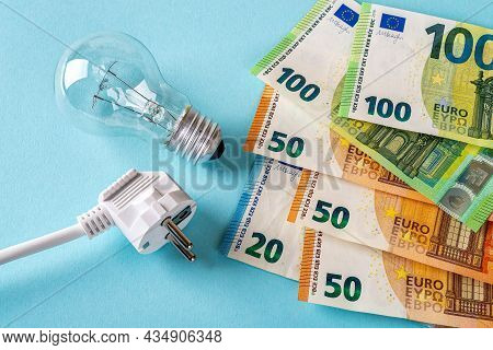 White Electric Plug, Light Bulb And Euro Money Banknotes Over Blue Background. Increasing Of Electri