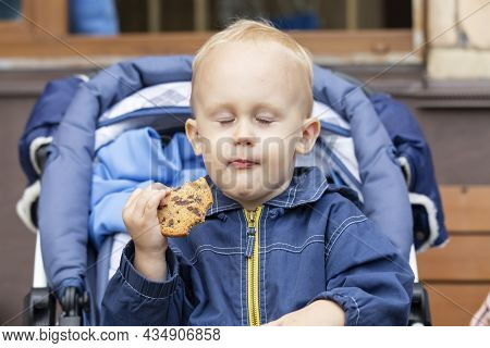 A Baby Is Sitting In A Stroller With A Cookie In His Hand