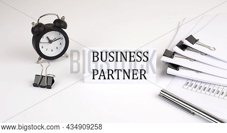 Card With Text Business Partner On A White Background, Near Office Supplies And Alarm Clock. Busines