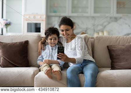 Smiling Bonding Young Indian Woman Using Cellphone With Small Kid.