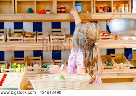 Little Preschool Girl Play With Food And Grocery Wooden Toys. Happy Active Child Playing Role Game A