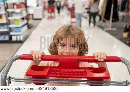 Close Up Portrait Of Child With Shopping Basket Purchasing Food In A Grocery Store. Customers Family