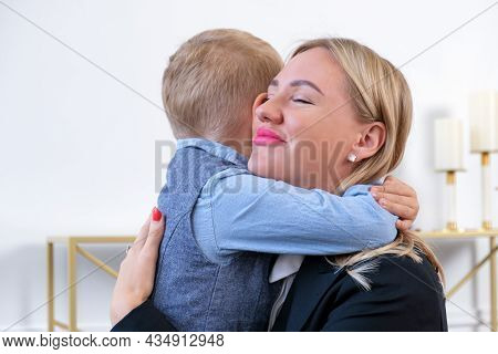 Gentle Hugs Of A Blonde Woman With Her Young Son. Mom Hugs The Baby. Relationship Between Parents An