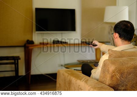 Man Watching Television On Sofa At Home, Sitting On A Sofa Watching Tv, Home Quarantine, New Normal,