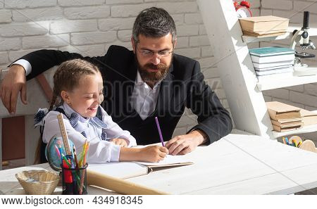Schoolgirl Studying And Writing In Classroom With Teacher. Cute Pupil Girl Studies With Happy Face E