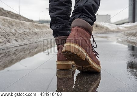 Close-up Of A Man In Brown Shoes Walking On Wet Asphalt In Spring. Snow All Around The Road