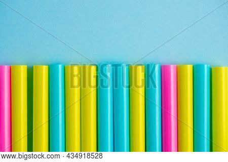 Close-up Of Multicolored Plastic Tubes On A Blue Paper Background. Top View, Flat Lay