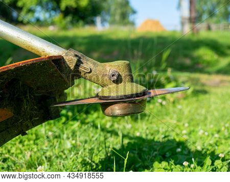 Close-up Of A Grass Trimmer With A Nozzle In The Form Of A Metal Knife. Site Maintenance, Grass Cutt