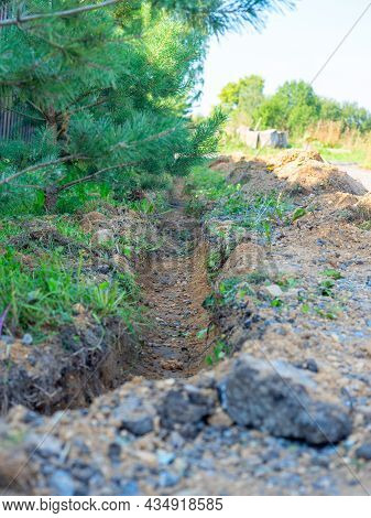 Close-up Of A Trench Dug In The Ground Along The Trees. Construction, Laying Of Communications Or In